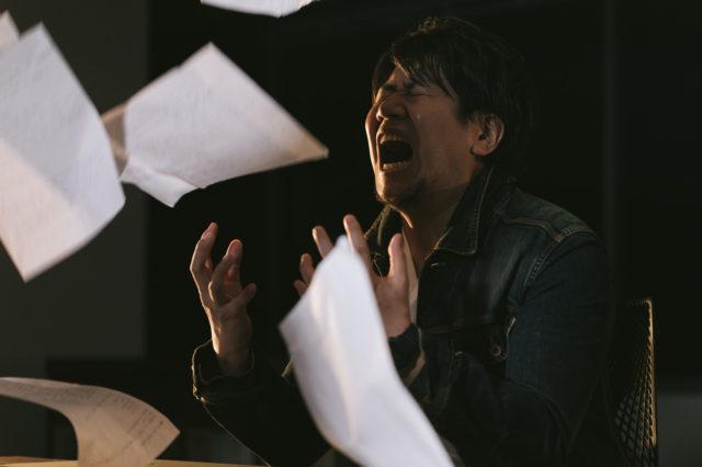 書類整理していてストレスが爆発する男性